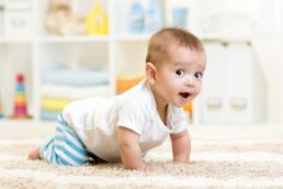 Bebê menino usando camiseta branca engatinhando em tapete e com olhar de surpresa