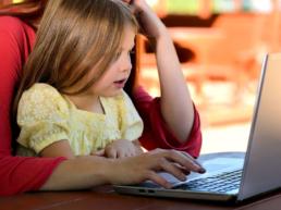 Menina usando vestido amarelo sentada em colo de mulher e em frente a um notebook