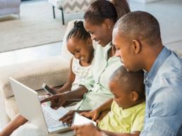 Familia composta por mulher homem e um casal de criancas sentados em um sofa olhando tela de notebook