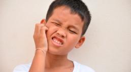 Menino coçando o rosto por causa da Caxumba