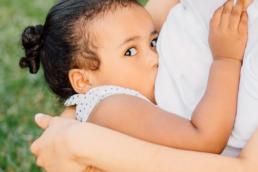 Uma mãe segurando sua filha no colo enquanto a amamenta