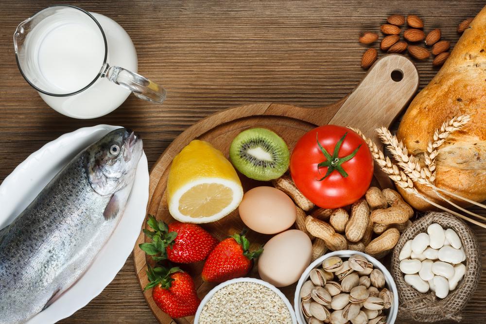 uma mesa com frutas, leite, peixe e castanhas
