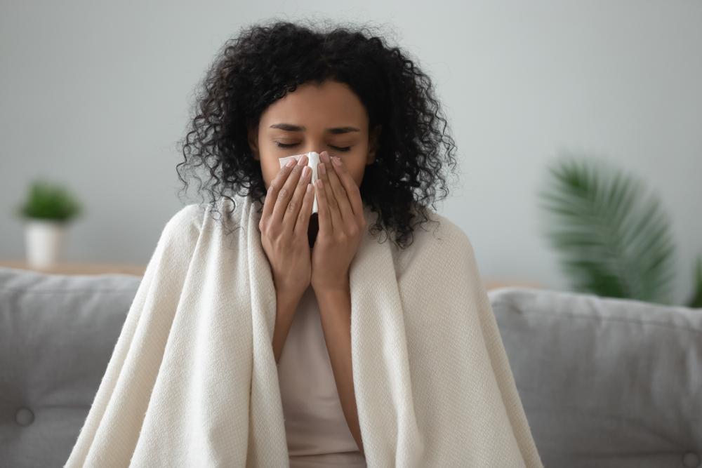 Uma mulher está sentada com um cobertor nas costas e assoando o nariz
