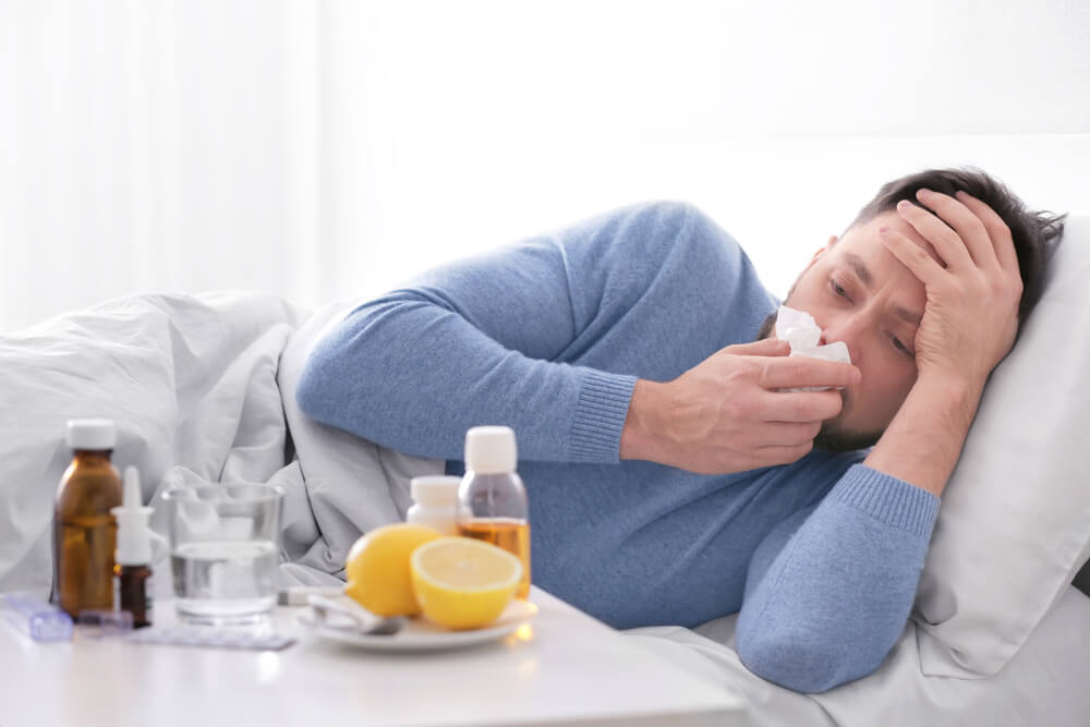 Um homem doente está deitado assoando o nariz. em frente tem uma mesa com alguns remédios