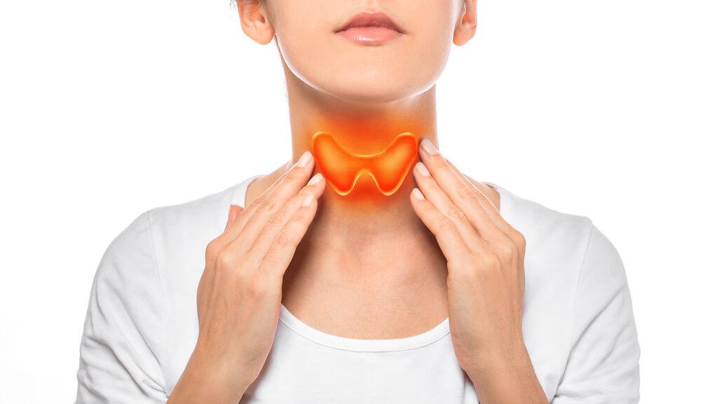 Uma mulher fazendo o autoexame da tireoide