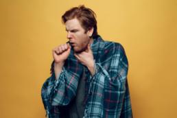 um homem coberto com uma manta azul enquanto está tossindo