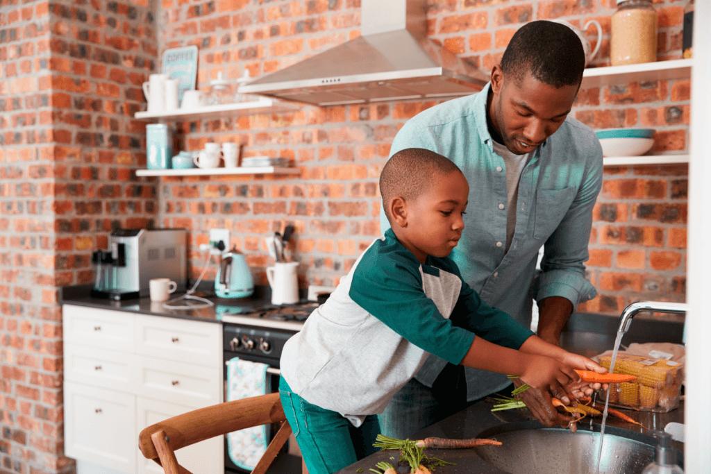 Um pai em pé ao lado de seu filho em cima de uma cadeira. Ambos estão apoiados em uma pia lavando os alimentos