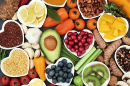 Visão de cima de uma mesa com várias frutas e legumes, como: abacate, uva, laranja, entre outras. Elas representam o post sobre qual exame que detecta falta de vitaminas