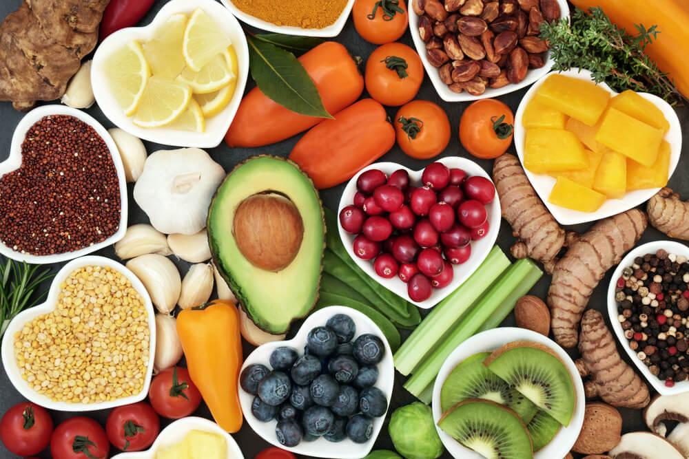 Visão de cima de uma mesa com várias frutas, legumes e grãos, como: abacate, uva, laranja, entre outras. Elas representam o post sobre qual nome do exame que detecta falta de vitaminas.