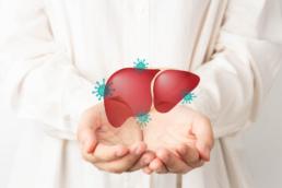 Pessoa com roupa branca com as duas mãos estendidas e em cima mostra uma ilustração do fígado com ilustração de vírus que é o órgão mais atingido pelos sintomas de hepatite b.