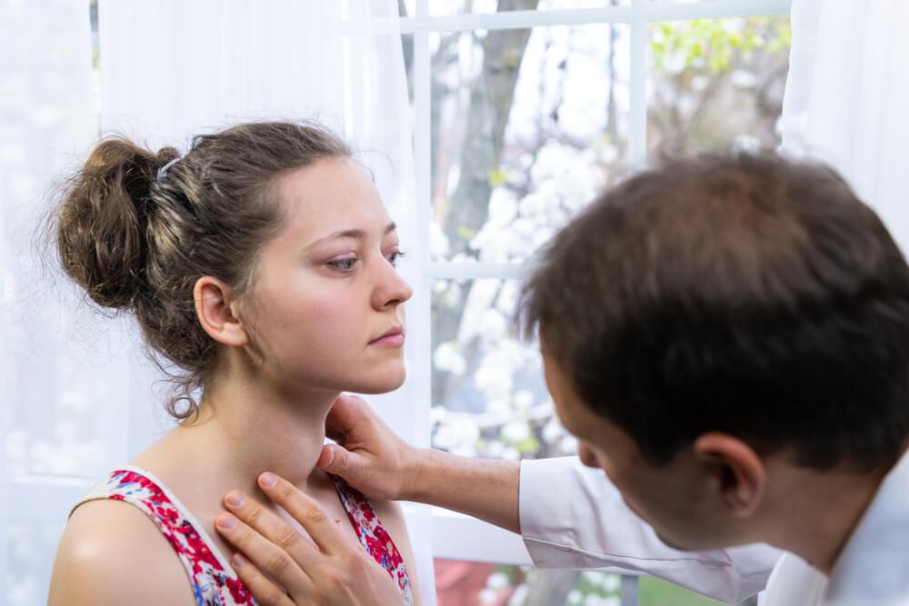 Médico toca o pescoço da paciente para ver se tem presença de nódulo na tireoide