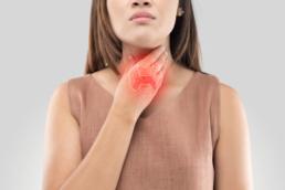 Mulher com a mão no pescoço, mais especificamente, colocando a mão em um nódulo na tireoide.