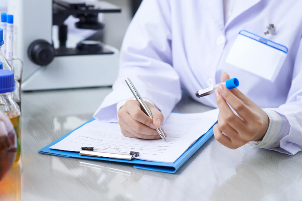 um médico segurando um tubo de ensaio com amostra de sangue e com a outra mão preenchendo uma ficha - o que é vcm no exame de sangue