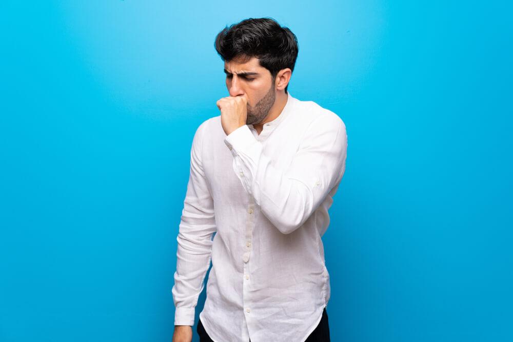 Homem com tosse seca, um dos sintomas mais comuns de Coqueluche
