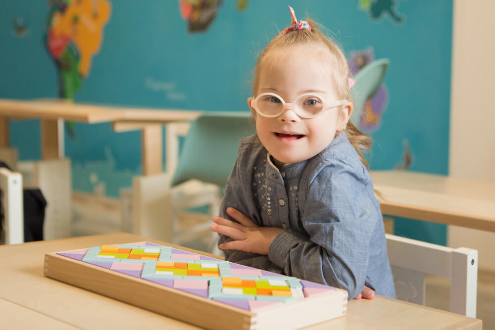 Menina com Síndrome de Down sentada em uma cadeira. Na sua frente um brinquedo em forma de mosaico. Ela está de braços cruzados e sorrindo olhando para a câmera