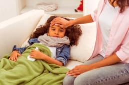 Mãe medindo a temperatura da filha resfriada. A imagem ilustra o post sobre a diferença entre gripe e resfriado.
