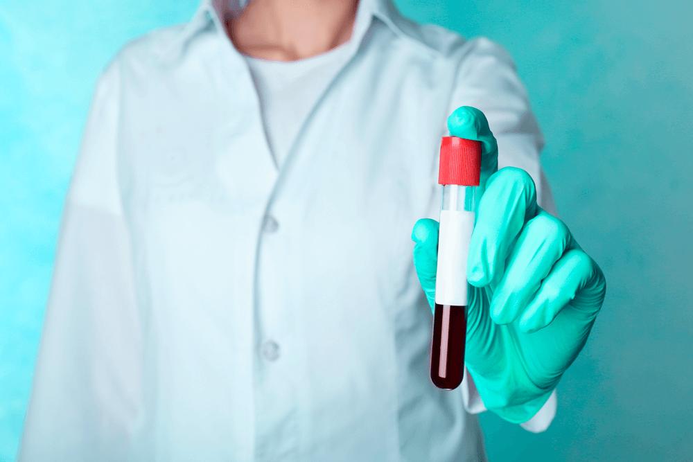 Enfermeiro segurando uma ampola de sangue que representa o exame NIPT