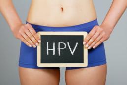 uma pessoa segurando uma placa escrito HPV segurando de frente para o quadril. o que é hpv