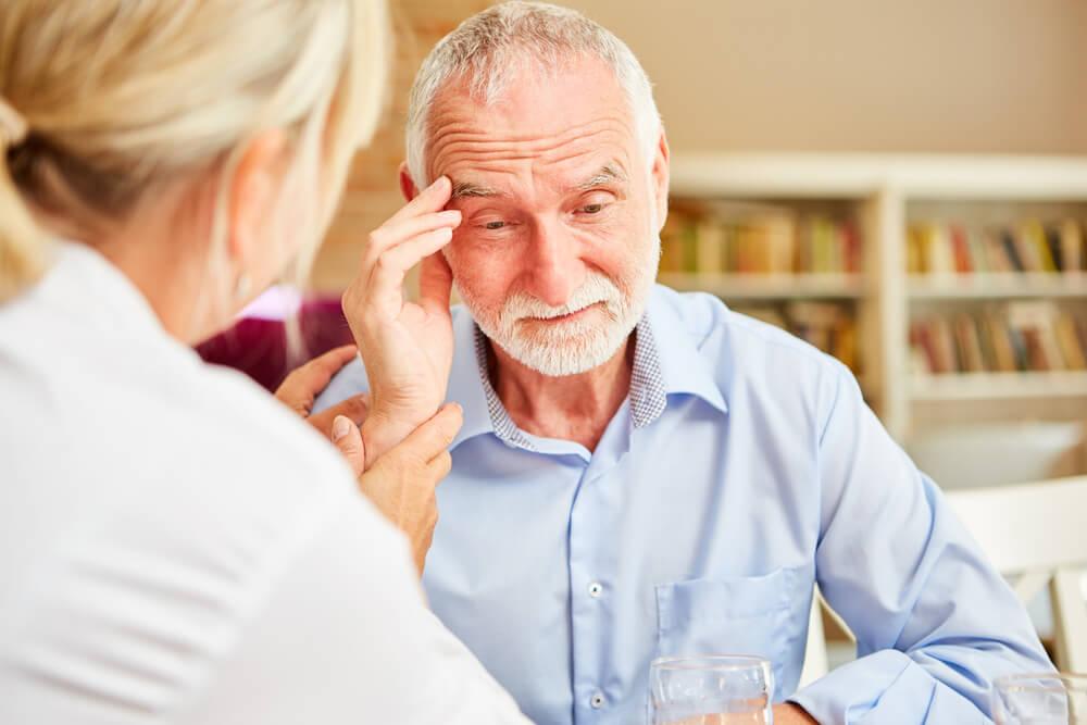 Idoso coloca a mão no rosto fazendo um sinal de esquecimento, um dos sintomas da doença de alzheimer