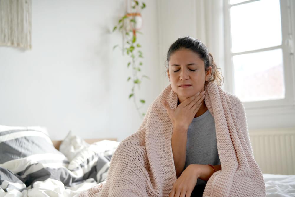 Mulher doente em cima da cama coloca a mão no pescoço como se estivesse com dor de garganta, representando a imagem principal do post sobre o que é difteria.