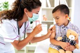 uma mulher profissional da saúde aplicando vacina no braço de um menino - vacina coqueluche