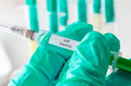 uma mão com luva verde segurando uma seringa com a descrição de vacina vip